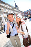 Cheerful couple showing visitor pass of Madrid