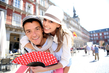 Man giving piggyback ride to girlfriend in Madrid