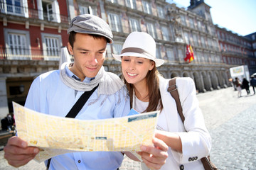 Couple of tourists looking at city map in Madrid