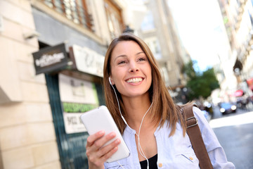 Cheerful girl using smartphone in town