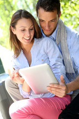 Couple websurfing on internet with tablet in park