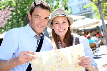 Couple in Santa Ana square of Madrid reading city map