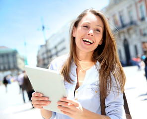 Cheerful girl with tablet walking in city