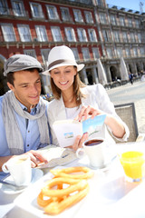 Cheerful couple looking at traveler guide in Madrid