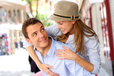 Man giving piggyback ride to girlfriend in town