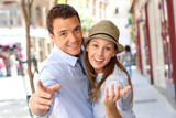 Cheerful couple pointing hand towards camera
