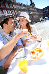 Cheerful couple of tourists eating churros in Madrid