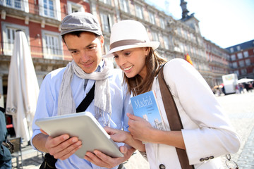 Couple visiting Madrid connected on digital tablet