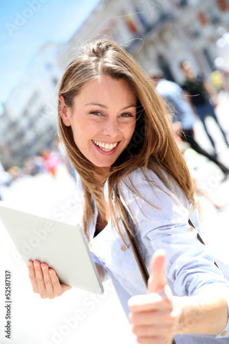 Cheerful girl with tablet showing thumb up