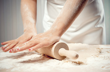 Woman rolling dough, close-up photo