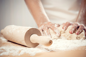 Woman kneading dough, close-up photo