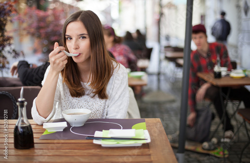 Young woman eating soup in an restaurant garden