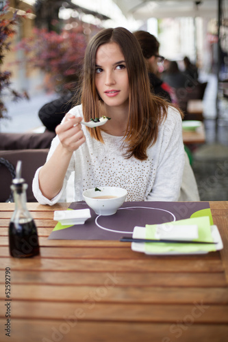 Pensive young woman eating soup in the restaurant
