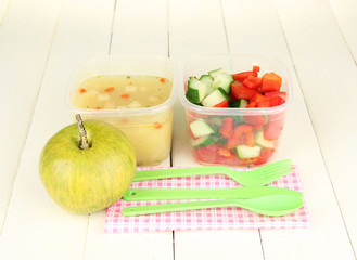 Tasty lunch in plastic containers, on wooden background