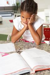 Fed Up Girl Doing Homework In Kitchen