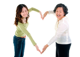 Asian senior woman and daughter making the sign of love