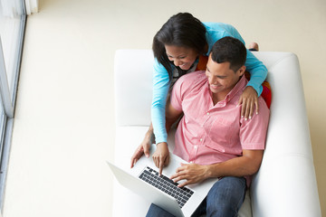 Overhead View Of Couple Relaxing On Sofa Using Laptop