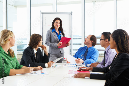 Businesswoman Conducting Meeting In Boardroom