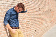 casual man standing upset by brick wall