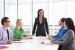 Businesswoman Conducting Meeting In Boardroom