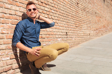 casual man crouching by wall & smiling