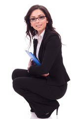 business woman with clipboard crouches