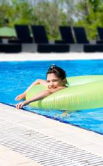 Девочка в надувном круге купается в бассейне