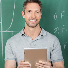 portrait lehrer mit tablet vor der tafel