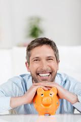 lächelnder mann stützt sich auf sparschwein
