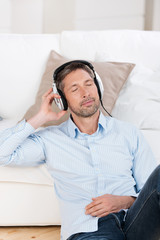 entspannter mann hört zuhause musik
