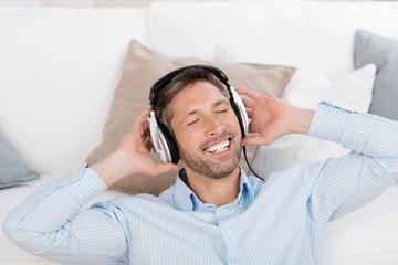 lächelnder mann genießt musik