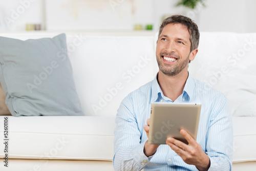 lachender mann mit tablet zu hause