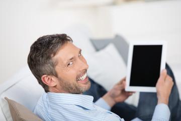 lächelnder mann liest zuhause am tablet