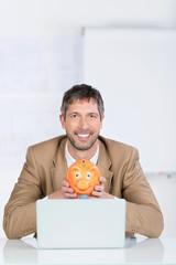 geschäftsmann mit sparschwein und laptop