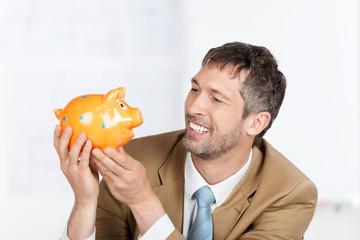 lachender geschäftsmann schaut auf  sparschwein