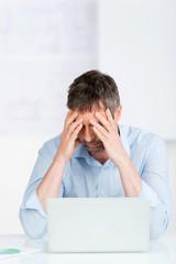 verzweifelter geschäftsmann am laptop