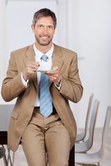 lächelnder geschäftsmann trinkt kaffee