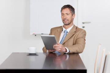 geschäftsmann im besprechungsraum schaut auf tablet