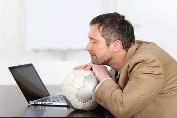 mann mit fu?ball vor dem laptop