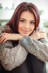 young happy beautiful woman in warm clothings at home