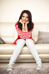 Smiling teen girl in colorful cloths sitting on the sofa