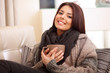 Happy woman sitting on sofa in cosy cloths with cup of coffee