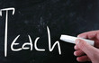 """Teach"" handwritten with white chalk on a blackboard"