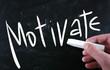 """Motivate"" handwritten with white chalk on a blackboard"