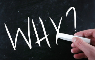 """Why"" handwritten with white chalk on a blackboard"