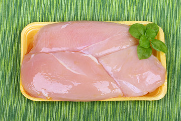 raw chicken breast in yellow plastic tray.