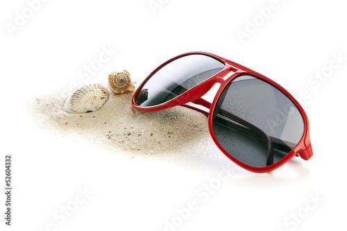 Sonnenbrille, Sand und Muscheln isoliert