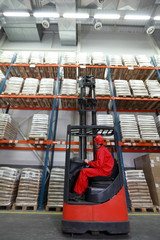 Worker  loading sacks with forklift loader in warehouse