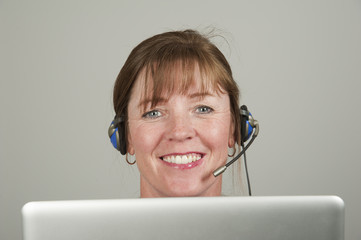 Woman using a headset and computer