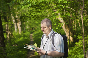 Hiker explores the map in the woods on trails